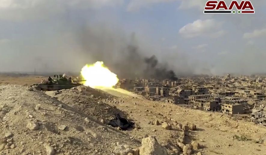 This frame grab from a video released on Nov. 2, 2017 by the Syrian official news agency SANA shows a Syrian army tank firing during a battle against Islamic State militants in Deir el-Zour, Syria. The Syrian army announced on Friday, Nov. 3, 2017, it liberated the long-contested eastern city of Deir el-Zour from the Islamic State group. (SANA via AP)