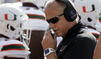 FILE - In this Saturday, Oct. 28, 2017, file photo, Miami head coach Mark Richt speaks into his headset during the first half of an NCAA college football game against North Carolina in Chapel Hill, N.C. Call it a semifinal Saturday in the Atlantic Coast Conference, with Miami and Virginia Tech meeting in a key Coastal Division matchup and Clemson visiting North Carolina State in a marquee Atlantic Division game. (AP Photo/Gerry Broome, File)