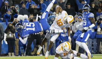 Kentucky quarterback Stephen Johnson dives into the end zone for a game-winning touchdown over Tennessee defensive back Nigel Warrior (18) and defensive back Shawn Shamburger (15) during the second half of an NCAA college football game Saturday, Oct. 28, 2017, in Lexington, Ky. Kentucky won the game 29-26. (AP Photo/David Stephenson)