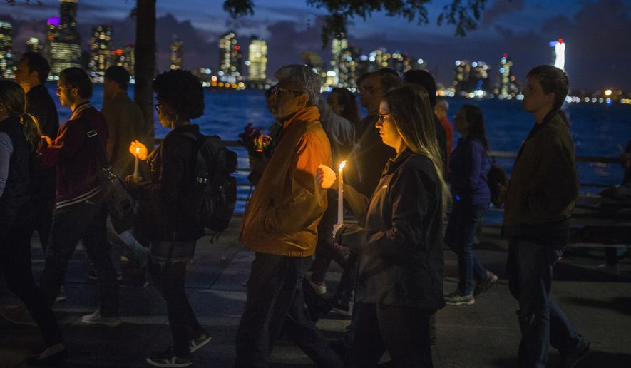 "People walk carrying lit candles along Hudson River during a vigil and memorial march near the crime scene to remember the victims of the recent truck attack on Thursday, Nov. 2, 2017, in New York. A man in a rental truck mowed down pedestrians and cyclists along the busy bike path near the World Trade Center memorial on Tuesday, killing at least eight people and seriously injuring others in what the mayor called ""a particularly cowardly act of terror."" (AP Photo/Andres Kudacki)"
