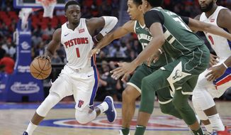 Detroit Pistons guard Reggie Jackson (1) drives around Milwaukee Bucks guard Malcolm Brogdon, center, and forward John Henson (31) during the first half of an NBA basketball game, Friday, Nov. 3, 2017, in Detroit. (AP Photo/Carlos Osorio)