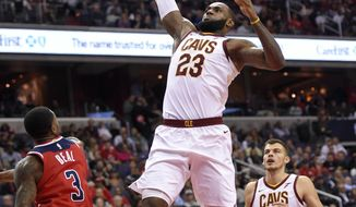 Cleveland Cavaliers forward LeBron James (23) goes to the basket against Washington Wizards guard Bradley Beal (3) during the first half of an NBA basketball game, Friday, Nov. 3, 2017, in Washington. Cavaliers forward Ante Zizic (41), of Croatia, watches. (AP Photo/Nick Wass)
