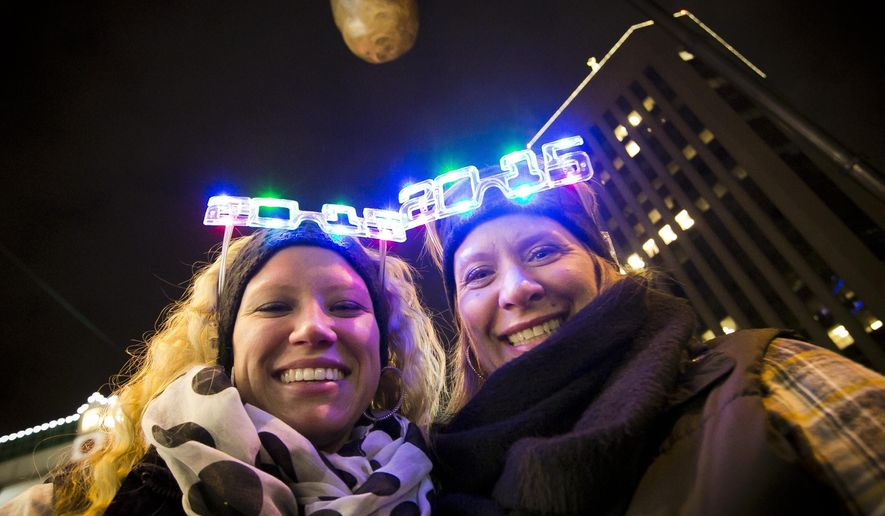 FILE--In this Dec. 31, 2014, file photo, Shelby Besler left, and her mother Tracey Besler, smile for a photograph on New Year's Eve as revelers ring in 2015 with the second annual Idaho Potato Drop in downtown Boise, Idaho. The Idaho Potato Commission has upped its sponsorship to $50,000 for the event, where a giant potato drops out of the sky as a countdown to the new year, that's now in its fifth year and keeps gaining more attention. (Darin Oswald/The Idaho Statesman via AP, file)