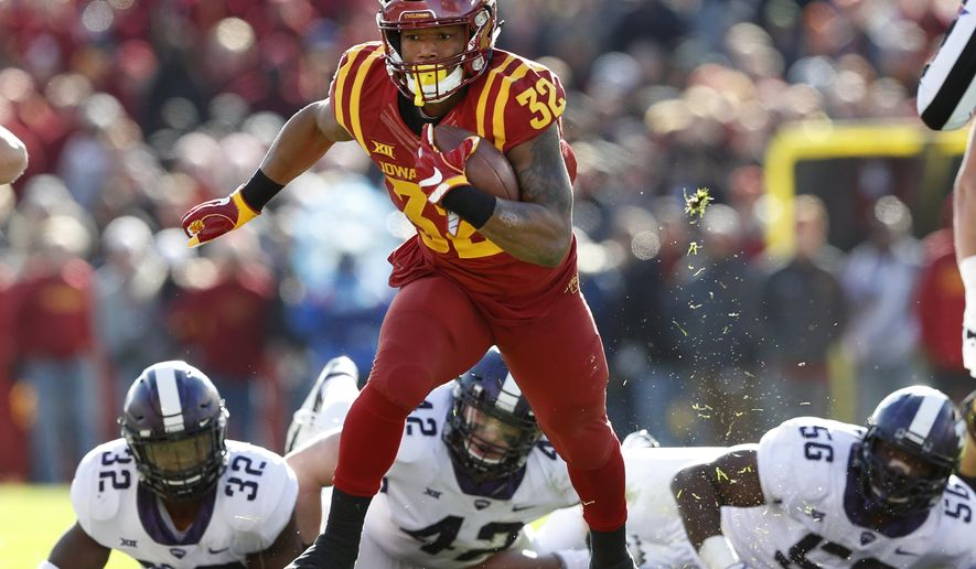 FILE - In this Oct. 28, 2017, file photo, Iowa State running back David Montgomery runs from TCU defenders Travin Howard (32), Ty Summers (42) and Chris Bradley (56) during the first half of an NCAA college football game, in Ames, Iowa. Montgomery leads the Big 12 with eight rushing touchdowns and is the second-leading rusher with 716 yards. Iowa State plays at West Virginia on Saturday, Nov. 4. (AP Photo/Charlie Neibergall, File)