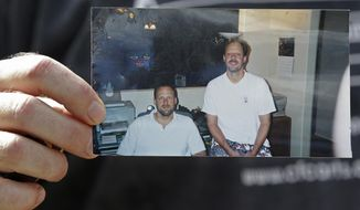 "FILE--In this Oct. 2, 2017, file photo, Eric Paddock holds a photo of himself, at left, with his brother, Stephen Paddock, who opened fire on the Route 91 Harvest Festival in Las Vegas, killing dozens and wounding hundreds, at his home in Orlando, Fla. The top lawman in Las Vegas says the gunman who killed 58 people at a concert last month had lost a significant amount of money in the previous two years and that it may be a ""determining factor"" in the worst mass shooting in modern U.S. history. (AP Photo/John Raoux, file)"