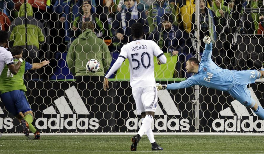 Vancouver Whitecaps goalie Stefan Marinovic, right, dives for a ball that crossed in front of the goal late in the first half of the second leg of an MLS soccer Western Conference semifinal against the Seattle Sounders, Thursday, Nov. 2, 2017, in Seattle. (AP Photo/Elaine Thompson)