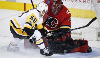 Pittsburgh Penguins' Jake Guentzel, left, tries to get the puck past Calgary Flames goalie Mike Smith during the third period of an NHL hockey game Thursday, Nov. 2, 2017, in Calgary, Alberta. (Jeff McIntosh/The Canadian Press via AP)