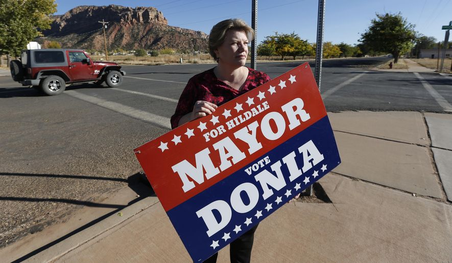 In this Thursday, Oct. 26, 2017 photo, Donia Jessop holds her mayoral campaign sign outside her store in Colorado City, Ariz. Campaign signs are unusual in a town where elections have long been quietly decided behind the scenes, with hand-picked men from the Fundamentalist Church of Jesus Christ of Latter-Day Saints running unopposed. (AP Photo/Rick Bowmer)