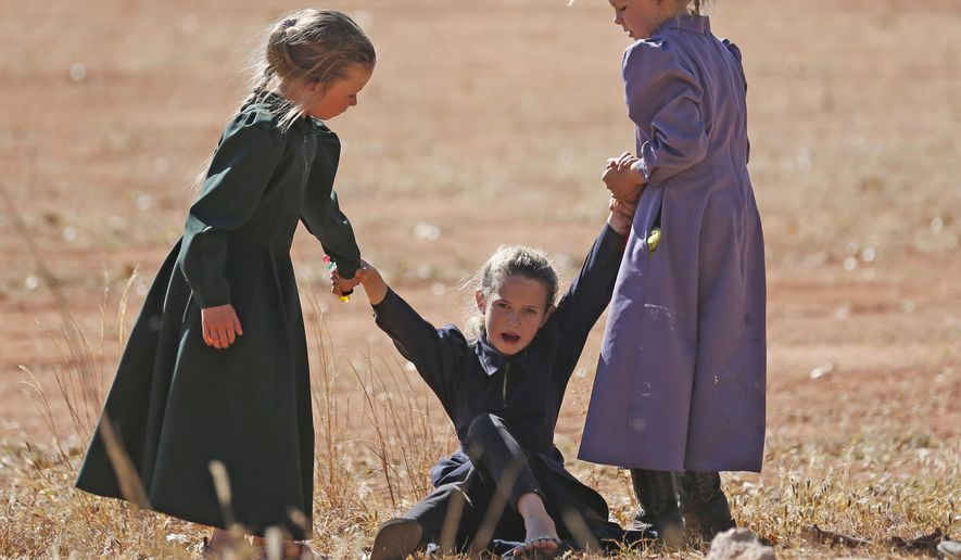 In this Wednesday, Oct. 25, 2017 photo, young girls play together in Colorado City, Ariz. The community on the Utah-Arizona border has been home for more than a century to a polygamous sect that is an offshoot of mainstream Mormonism. The community is undergoing a series of changes as the sect's control of the town slips away amid government evictions and crackdowns. (AP Photo/Rick Bowmer)