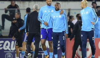 Marseille's Patrice Evra, center right, is led away by his teammate Rolando after a scuffle with Marseille supporters who trespassed into the field before the Europa League group I soccer match between Vitoria SC and Olympique de Marseille at the D. Afonso Henriques stadium in Guimaraes, Portugal, Thursday, Nov. 2, 2017. Evra was shown a red card before the start of the match for his involvement in the incident. (AP Photo/Luis Vieira)