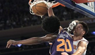 New York Knicks forward Doug McDermott, right, dunks the ball over Phoenix Suns forward Josh Jackson (20) during the second quarter of an NBA basketball game Friday, Nov. 3, 2017, at Madison Square Garden in New York. (AP Photo/Bill Kostroun)