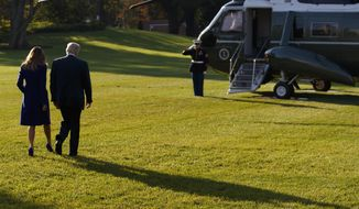 First lady Melania Trump looks and President Donald Trump walk to board Marine One on the South Lawn of the White House for a trip to Asia, Friday, Nov. 3, 2017, in Washington. (AP Photo/Evan Vucci)
