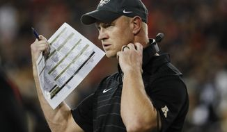 FILE - In this Saturday, Oct. 7, 2017, file photo, UCF head coach Scott Frost works the sidelines in the first half of an NCAA college football game against Cincinnati in Cincinnati. No. 15 UCF is undefeated and SMU is already bowl eligible going into the first weekend in November. The high-scoring American Athletic Conference teams now go head-to-head.  (AP Photo/John Minchillo, File)