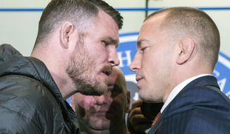 FILE - In this Oct. 13, 2017, file photo, Britain's Michael Bisping, left, and Canada's Georges St. Pierre face off during a news conference in Toronto, to promote their upcoming UFC 217. At center rear is UFC President Dana White. The pair square off on Saturday at Madison Square Garden in New York. (Chris Young/The Canadian Press via AP, File)