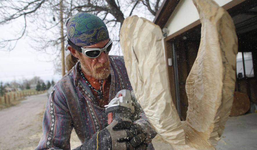 In this Friday, Oct. 27, 2017 photo, Forest Cunningham, a Cheyenne native, carves an intricate personal project in his mother's backyard in east Cheyenne, Wyo. When Forest Cunningham looks at sections of fallen trees and logs, he doesn't only see pieces of wood. Instead, he sees a friendly bear or a snake with a sideways grin or a fierce bald eagle, all waiting for him to set them free.  (Jacob Byk/The Wyoming Tribune Eagle via AP)