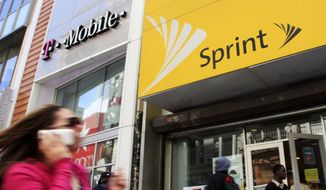 In this April 27, 2010, file photo, a woman using a cell phone walks past T-Mobile and Sprint stores in New York. (AP Photo/Mark Lennihan, File)