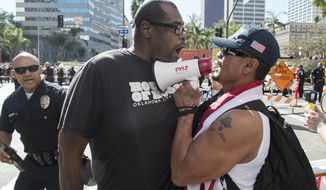 """An anti Trump protester, left, confronts a counter protester and Trump supporter during """"This Nightmare Must End: the Trump/Pence Regime Must Go!"""" protest in downtown Los Angeles, Saturday, Nov. 4, 2017. The group Refuse Fascism called for protests against President Donald Trump's administration in several major cities on Saturday, including Los Angeles. (Ed Crisostomo/Los Angeles Daily News via AP)"""