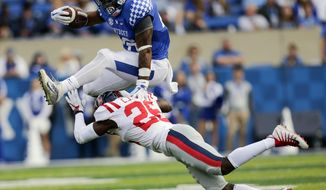 Kentucky running back Benny Snell Jr., top, leaps over Mississippi defensive back C.J. Moore during the first half of an NCAA college football game Saturday, Nov. 4, 2017, in Lexington, Ky. (AP Photo/David Stephenson)