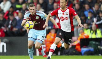 Burnley's Chris Wood, left, and Southampton's Maya Yoshida chase the ball during their English Premier League soccer match at St Mary's Stadium in Southampton, England, Saturday Nov. 4, 2017. (Adam Davy/PA via AP)