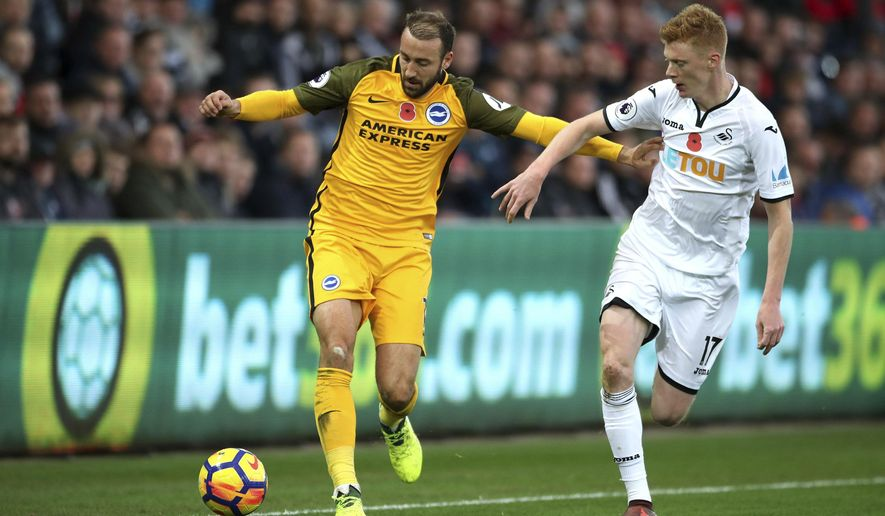Brighton & Hove Albion's Glenn Murray, left, and Swansea City's Sam Clucas battle for the ball during the English Premier League soccer match at the Liberty Stadium, Swansea, Wales, Saturday Nov. 4, 2017. (Nick Potts/PA via AP)