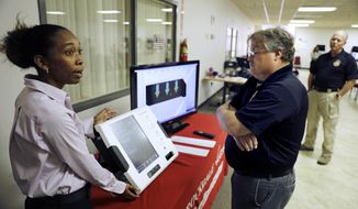 In this Thursday, Oct. 19, 2017 photo, Renee Phifer, Rockdale County board of elections assistant director, left, demonstrates a new voting machine at a polling site to Kelly Monroe, investigator with the Georgia secretary of state office in Conyers, Ga. Last summer, a security expert came across a gaping hole in Georgia's election management system. The revelation prompted a lawsuit seeking to compel Georgia to toss all of its touchscreen voting machines and replace them with a system that provides a paper record of every ballot cast. Georgia is one of five states where no such record exists. (AP Photo/David Goldman)