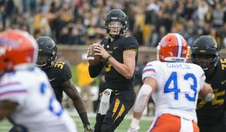 Missouri quarterback Drew Lock looks for an open receiver between Florida defenders during the first half of an NCAA college football game Saturday, Nov. 4, 2017, in Columbia, Mo. (AP Photo/L.G. Patterson)