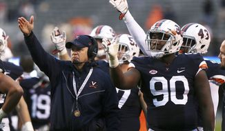 Virginia head coach Bronco Mendenhall, left, and Steven Wright (90) gesture as they wait for officials to review a play during the second half of an NCAA college football game against Georgia Tech, Saturday, Nov. 4, 2017, in Charlottesville, Va. (AP Photo/Zack Wajsgras)