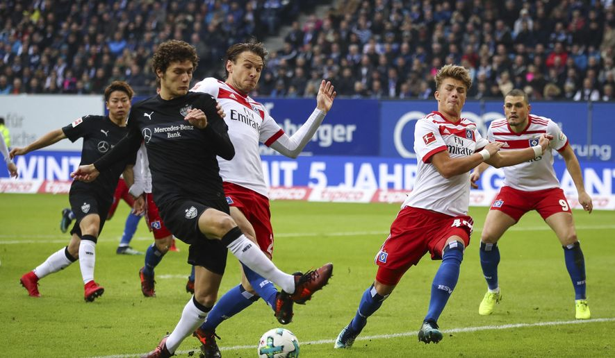 Stuttgart's Benjamin Pavard, left, and Hamburg's Albin Ekdal , center and Jann-Fiete Arp, second right, challenge for the ball  during the German Bundesliga soccer match between Hamburger SV and VfB Stuttgart in Hamburg, Germany, Saturday, Nov. 4, 2017. (Christian Charisius/dpa via AP)