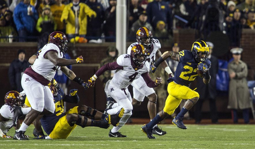 Michigan running back Karan Higdon (22) rushes ahead of Minnesota defensive back Adekunle Ayinde (4) in the first quarter of an NCAA college football game in Ann Arbor, Mich., Saturday, Nov. 4, 2017. (AP Photo/Tony Ding)an