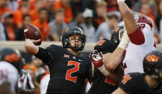 Oklahoma State quarterback Mason Rudolph (2) passes under pressure in the second half of an NCAA college football game against Oklahoma in Stillwater, Okla., Saturday, Nov. 4, 2017. Oklahoma won 62-52. (AP Photo/Sue Ogrocki)