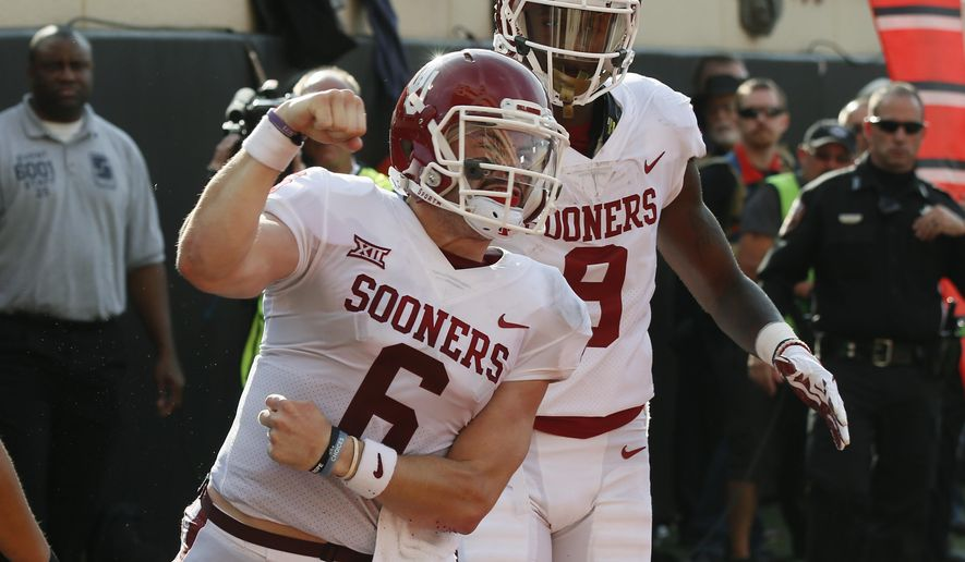 Oklahoma quarterback Baker Mayfield (6) celebrates a touchdown against Oklahoma State in the first half of an NCAA college football game in Stillwater, Okla., Saturday, Nov. 4, 2017. Oklahoma wide receiver CeeDee Lamb is at right. (AP Photo/Sue Ogrocki)
