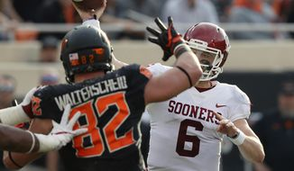 Oklahoma quarterback Baker Mayfield (6) throws under pressure from Oklahoma State defensive end Cole Walterscheid (82) in the first half of an NCAA college football game in Stillwater, Okla., Saturday, Nov. 4, 2017. (AP Photo/Sue Ogrocki)