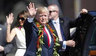 Adorned with lei, President Donald Trump walks towards the motorcade with first lady Melania Trump to meet servicemen , Friday, Nov. 3, 2017 at Joint Base Pearl Harbor Hickam in Honolulu. (Jamm Aquino/The Star-Advertiser via AP)