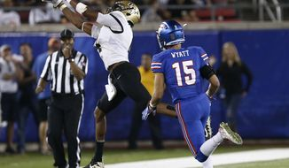 Central Florida wide receiver Tre'Quan Smith (4) makes the catch as SMU defensive back Jordan Wyatt (15) defends during the first half of an NCAA college football game, Saturday, Nov. 4, 2017, in Dallas. (AP Photo/Mike Stone)