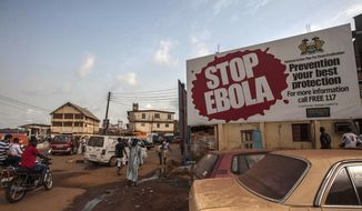 FILE - In this Friday, Jan. 15, 2016 file photo, people pass a banner reading 'STOP EBOLA' forming part of Sierra Leone's Ebola free campaign in the city of Freetown, Sierra Leone. Fraud by Red Cross workers and others wasted more than $6 million meant to fight the deadly Ebola outbreak in West Africa, the organization confirmed Saturday, Nov. 4, 2017. The revelations follow an internal investigation of how money was handled during the 2014-2016 epidemic that killed more than 11,000 people in Sierra Leone, Liberia and Guinea. (AP Photo/Aurelie Marrier d'Unienville, file)