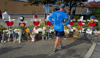 CORRECTS TO HOUSTON NOT CHAMBERS STREET A passerby pauses at a makeshift memorial near a bike path that honors victims of an attack who were stuck and killed by a rental truck driven by indicted suspect Sayfullo Saipov last Tuesday, at Houston and West Streets in New York, Saturday, Nov. 4, 2017. Saipov is accused of using the rental truck to mow down pedestrians and cyclists along the busy bike path. (AP Photo/Craig Ruttle)