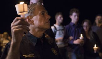 Texas Gov. Greg Abbott participates in a candlelight vigil for the victims of a fatal shooting at the First Baptist Church in Sutherland Springs, Sunday, Nov. 5, 2017, in Sutherland Springs, Texas. A man opened fire inside of the church in the small South Texas community on Sunday, killing more than 20 people. (AP Photo/Darren Abate)
