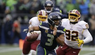 Seattle Seahawks quarterback Russell Wilson (3) scrambles away from Washington Redskins defensive end Stacy McGee (92) in the second half of an NFL football game, Sunday, Nov. 5, 2017, in Seattle. (AP Photo/Stephen Brashear)