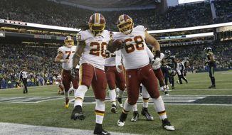 Washington Redskins running back Rob Kelley (20) celebrates with offensive guard Tyler Catalina (68) after Kelley scored a touchdown in the second half of an NFL football game against the Seattle Seahawks, Sunday, Nov. 5, 2017, in Seattle. The Redskins won 17-14. (AP Photo/Elaine Thompson)