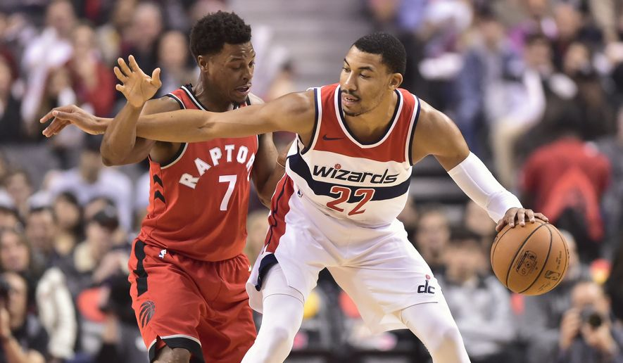 Washington Wizards forward Otto Porter Jr. (22) dribbles the ball under pressure from Toronto Raptors guard Kyle Lowry (7) during first-half NBA basketball game action in Toronto, Sunday, Nov. 5, 2017. (Frank Gunn/The Canadian Press via AP)