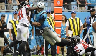 Carolina Panthers' Cam Newton (1) dives over the goal line for a touchdown against Atlanta Falcons' Desmond Trufant (21) and Deion Jones (45) in the first half of an NFL football game in Charlotte, N.C., Sunday, Nov. 5, 2017. (AP Photo/Mike McCarn)