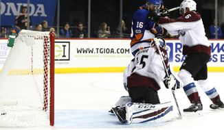 A shot by New York Islanders defenseman Johnny Boychuk (not shown) slides into the crease behind Colorado Avalanche goalie Jonathan Bernier (45) for the Islanders fifth goal during the second period of an NHL hockey game in New York, Sunday, Nov. 5, 2017. Colorado Avalanche defenseman Erik Johnson (6) fends off New York Islanders left wing Andrew Ladd (16) after the play. (AP Photo/Kathy Willens)