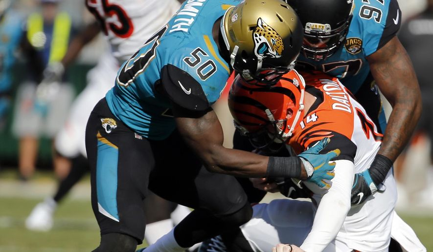 Jacksonville Jaguars linebacker Telvin Smith (50) and defensive lineman Malik Jackson (97) sack Cincinnati Bengals quarterback Andy Dalton (14) during the second half of an NFL football game, Sunday, Nov. 5, 2017, in Jacksonville, Fla. (AP Photo/Stephen B. Morton)