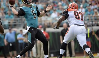 Jacksonville Jaguars quarterback Blake Bortles (5) throws a pass as he is rushed by Cincinnati Bengals defensive tackle Geno Atkins (97) during the first half of an NFL football game, Sunday, Nov. 5, 2017, in Jacksonville, Fla. (AP Photo/Phelan M. Ebenhack)