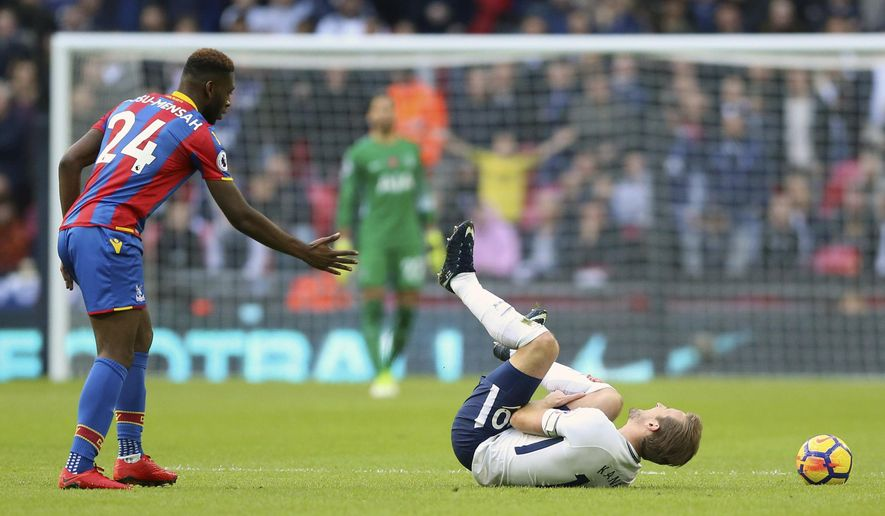 Tottenham Hotspur's Harry Kane, right,  reacts after a tackle from Crystal Palace's Timothy Fosu-Mensah, during the English Premier League soccer match between Tottenham Hotspur and Crystal Palace, at Wembley Stadium, in London, Sunday, Nov. 5, 2017. (Nigel French/PA via AP)