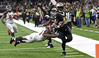 New Orleans Saints running back Alvin Kamara (41) carries for a touchdown past a diving Tampa Bay Buccaneers defensive tackle Clinton McDonald in the first half of an NFL football game in New Orleans, Sunday, Nov. 5, 2017. (AP Photo/Bill Feig)