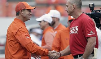 Clemson head coach Dabo Swinney and North Carolina State head coach Dave Doeren shake hands prior to an NCAA college football game in Raleigh, N.C., Saturday, Nov. 4, 2017. (AP Photo/Gerry Broome)