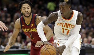 Atlanta Hawks' Dennis Schroder (17), from Germany, looks to pass against Cleveland Cavaliers' Derrick Rose (1) in the first half of an NBA basketball game, Sunday, Nov. 5, 2017, in Cleveland. (AP Photo/Tony Dejak)