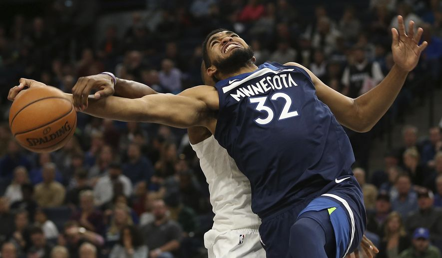 Minnesota Timberwolves center Karl-Anthony Towns (32) gets tangled up with Charlotte Hornets center Dwight Howard, left, in the first half of an NBA basketball game, Sunday, Nov. 5, 2017, in Minneapolis. (AP Photo/Stacy Bengs)