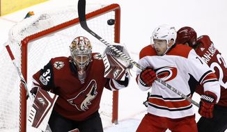 Carolina Hurricanes center Derek Ryan (7) tries to redirect the puck in front of Arizona Coyotes goalie Antti Raanta (32) as Coyotes' Oliver Ekman-Larsson, right, defends during the third period of an NHL hockey game Saturday, Nov. 4, 2017, in Glendale, Ariz. The Coyotes defeated the Hurricanes 2-1 in a shootout. (AP Photo/Ross D. Franklin)